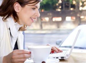 happy businesswoman drinking morning coffee and surfing internet